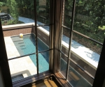 view of the stair window with the pool in the background